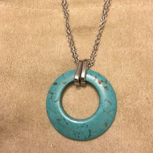 One turquoise colored necklace with chain.